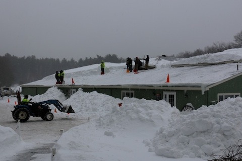clearing snow from the barn roof
