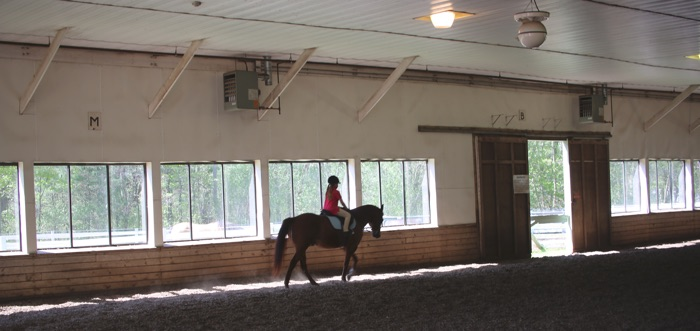 Chrislar Indoor Arena with student riding a horse